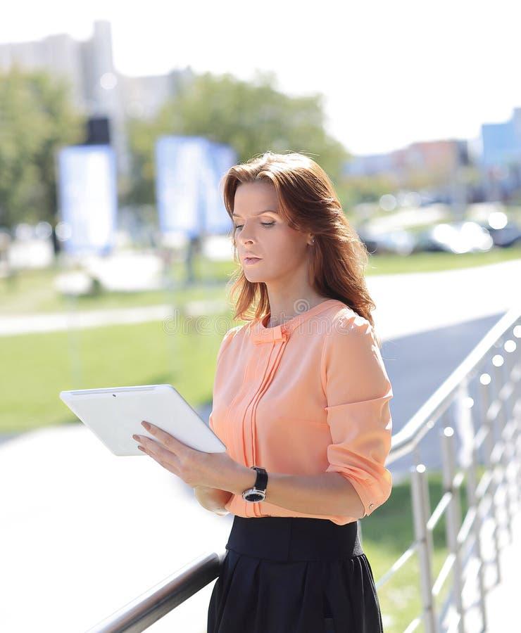 Poważna młoda kobieta z cyfrową pastylką na zamazanym miasta tle obraz stock