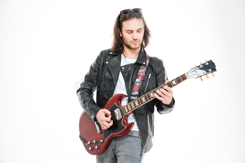 Poważna młoda męska gitarzysta pozycja i bawić się gitara elektryczna zdjęcie stock