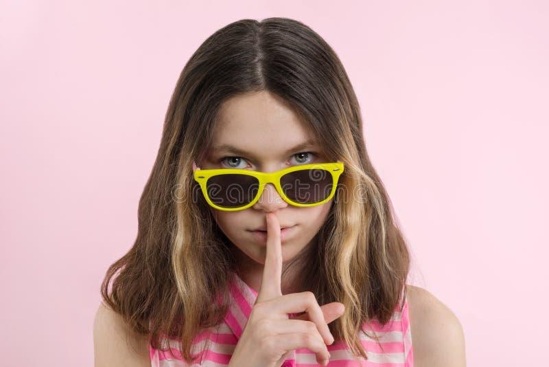 Poważna nastoletnia dziewczyna 13,14 roku w jaskrawych żółtych szkłach pokazuje daleko cisza znaka obraz royalty free
