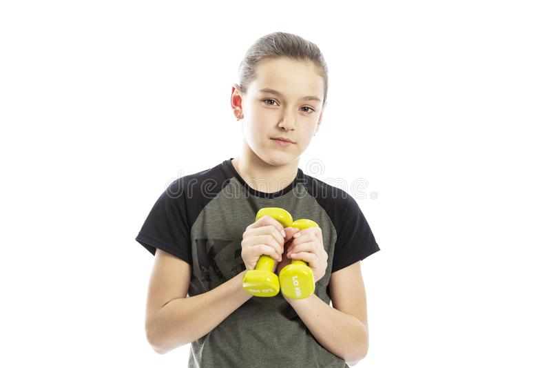 Poważna nastoletnia dziewczyna z dumbbells w ich rękach pojedynczy bia?e t?o obrazy royalty free