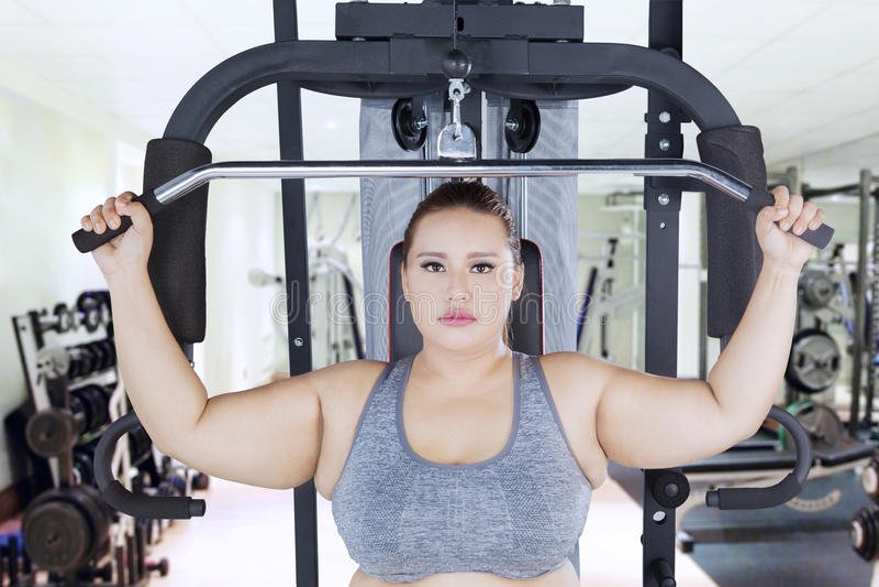 Poważna otyła kobieta ćwiczy na sprawności fizycznej centrum fotografia royalty free