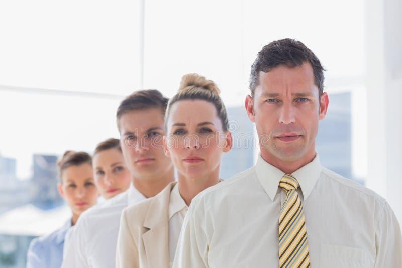 Poważna przystojna biznesmen pozycja z drużyną zdjęcia royalty free