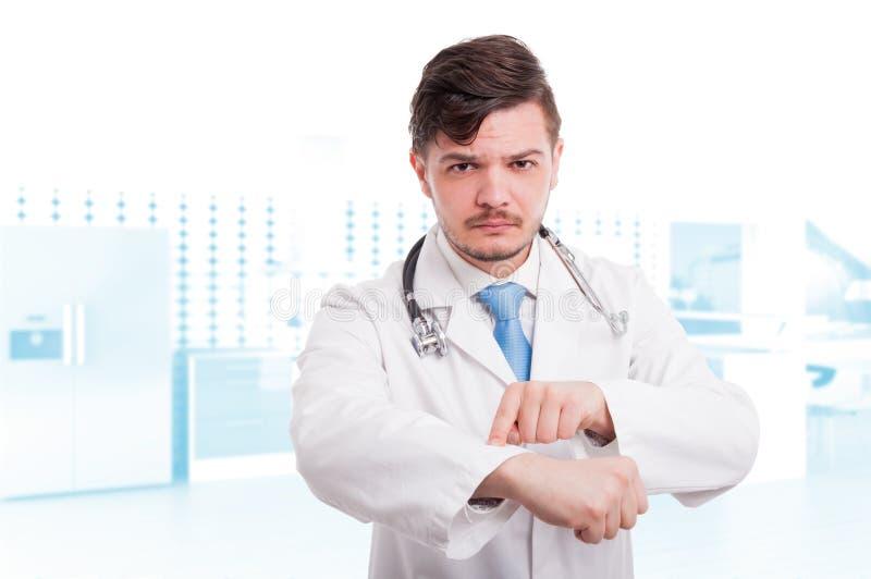 Poważna samiec lekarka wskazuje jego wristwatch zdjęcia royalty free