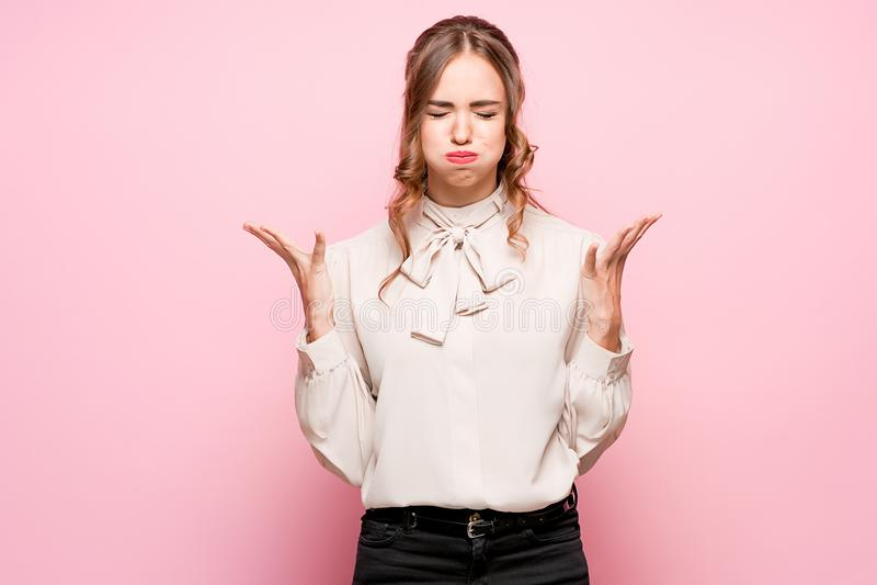 Poważna sfrustowana młoda piękna biznesowa kobieta na różowym tle zdjęcia royalty free