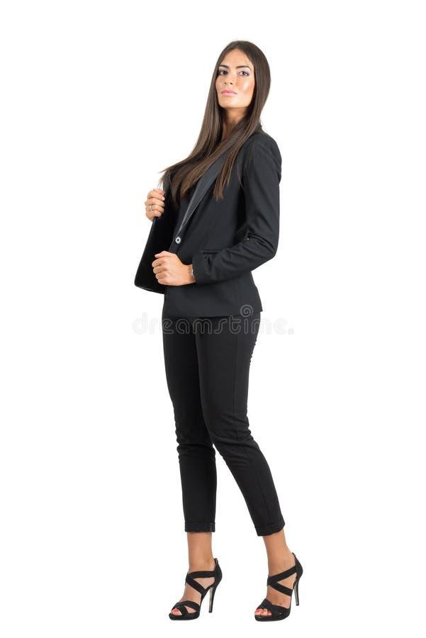 Poważna silna seksowna biznesowa kobieta w czarnym kostiumu pozuje przy kamerą obrazy royalty free
