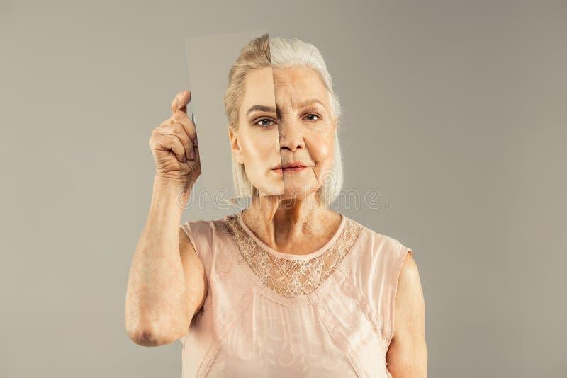 Poważna starzejąca się kobieta trzyma lustrzany pobliskiego jej twarz obraz royalty free