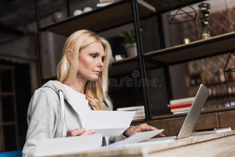 poważna w średnim wieku kobieta robi papierkowej robocie i używa laptop zdjęcia royalty free