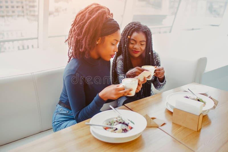 Poważne młode afrykańskie kobiety siedzą w kawiarni Trzymają filiżanka kawy i telefon Modele patrzeją skoncentrowanymi fotografia stock