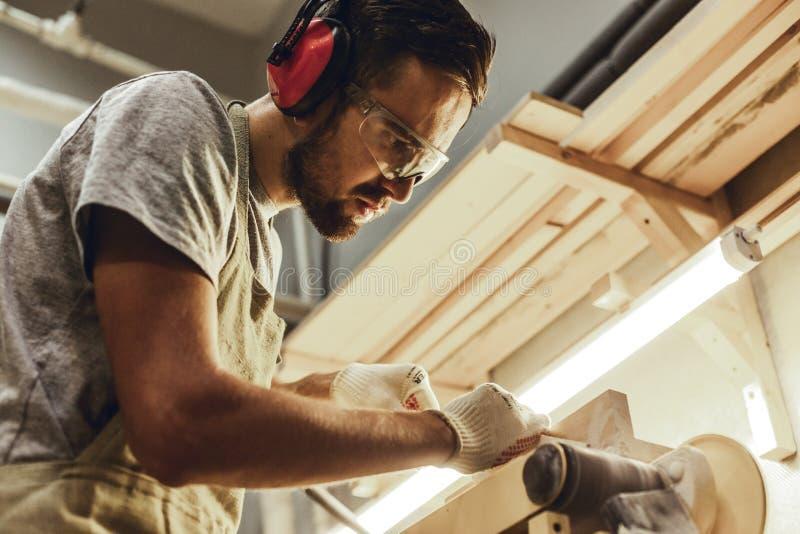 Poważnego cieśli kształtująca drewniana część na pasowym sander fotografia royalty free
