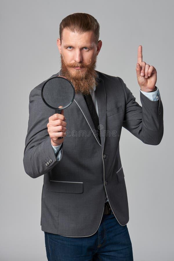 Poważnego modnisia biznesowy mężczyzna z powiększać - szkło fotografia stock