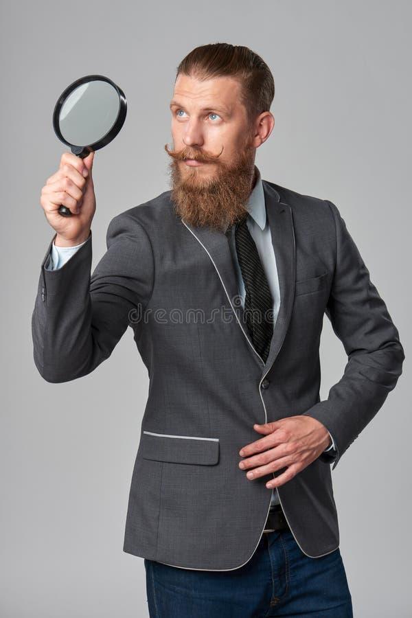 Poważnego modnisia biznesowy mężczyzna z powiększać - szkło fotografia royalty free