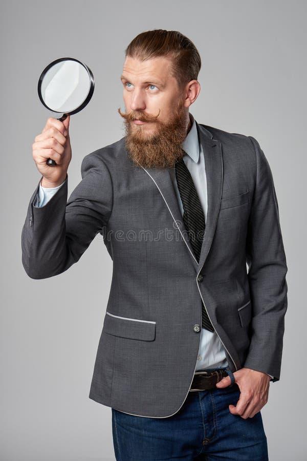 Poważnego modnisia biznesowy mężczyzna z powiększać - szkło obrazy stock