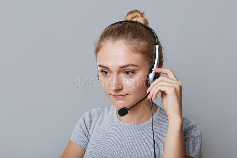 Poważni żeńscy helpline operatora uses hełmofony dla ona praca, skupiający się na coś, odizolowywający nad popielatym tłem Biznes zdjęcia stock