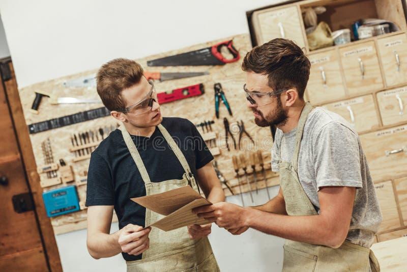 Poważni rzemieślnicy dyskutuje dokumenty obrazy stock