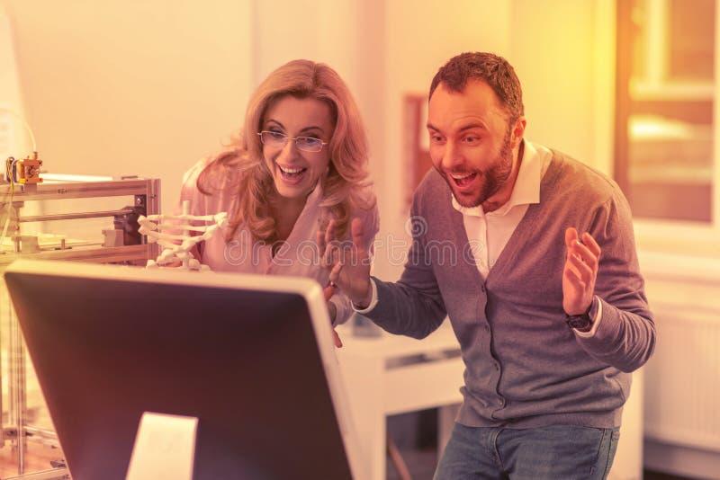 Poważnie mężczyzna i kobieta ekscytujący widzieć wielkich rezultaty ich praca fotografia stock