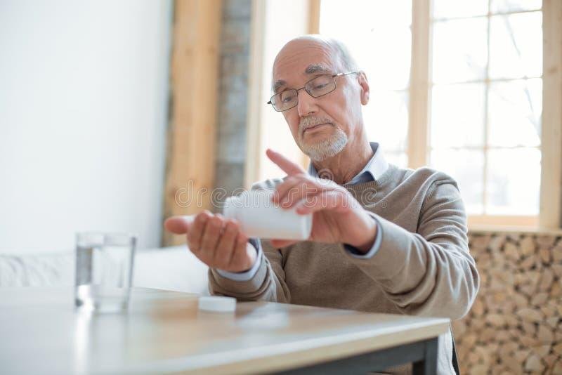 Poważnie starszy mężczyzna bierze lekarstwo obraz stock
