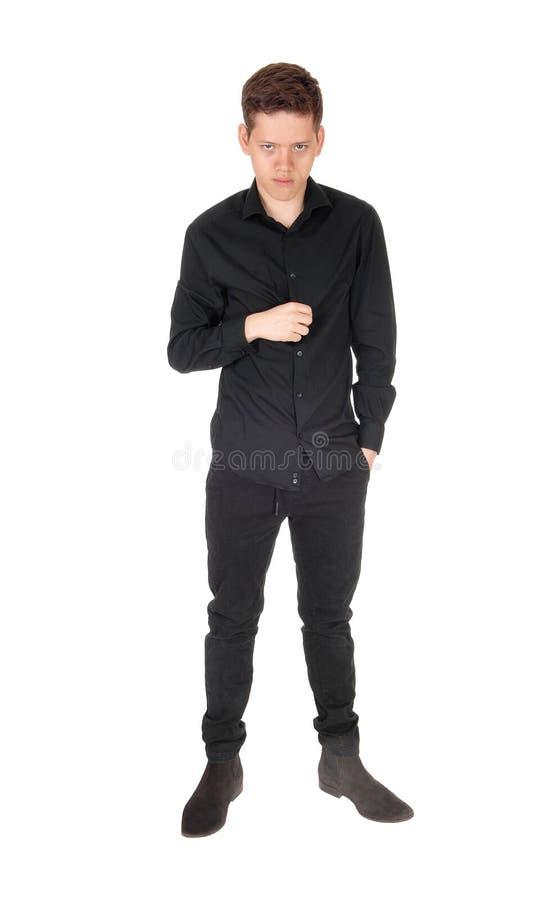 Poważnie wyglądający nastolatek w czarnym stroju zdjęcie royalty free