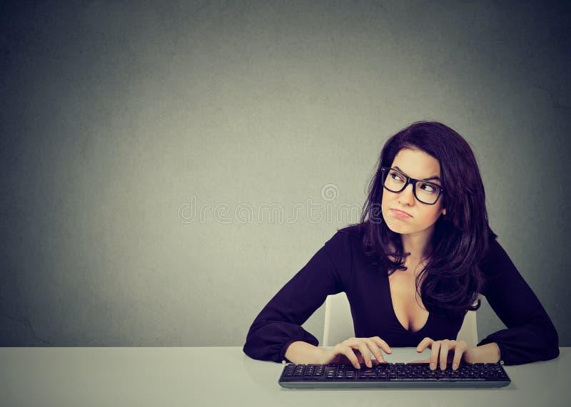 Poważny absorbujący młodej kobiety obsiadanie przy biurkiem pisać na maszynie na klawiaturze desktop obraz royalty free