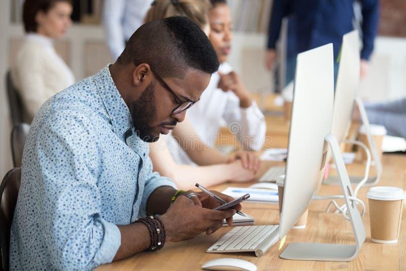 Poważny amerykanin afrykańskiego pochodzenia mężczyzna używa smartphone przy miejsce pracy obraz stock
