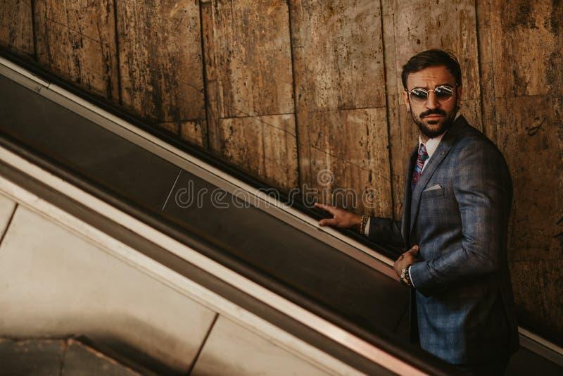 Poważny biznesmen iść w górę eskalatoru na podczas gdy trzymający dźwigarki fotografia stock