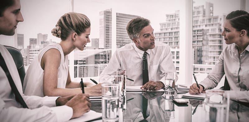 Poważny biznesmen podczas spotkania opowiada jego pracownicy obrazy royalty free