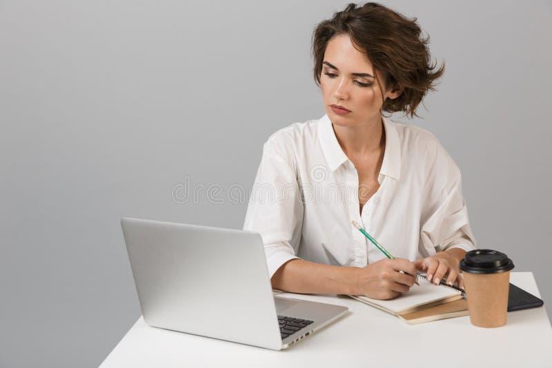 Poważny biznesowej kobiety pozować odizolowywam nad popielatym ściennym tła obsiadaniem przy stołowym używa laptopem zdjęcia royalty free