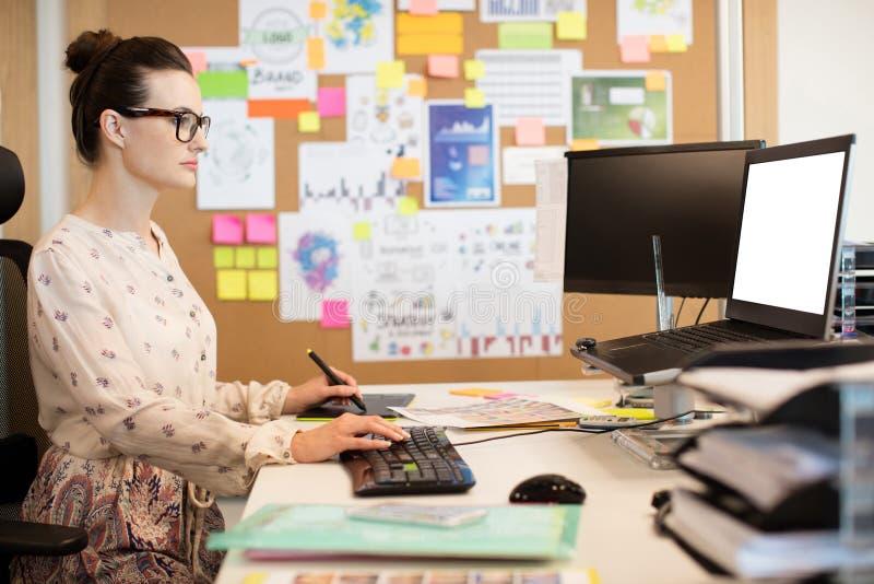 Poważny bizneswoman pracuje na digitizer podczas gdy używać klawiaturę zdjęcie royalty free