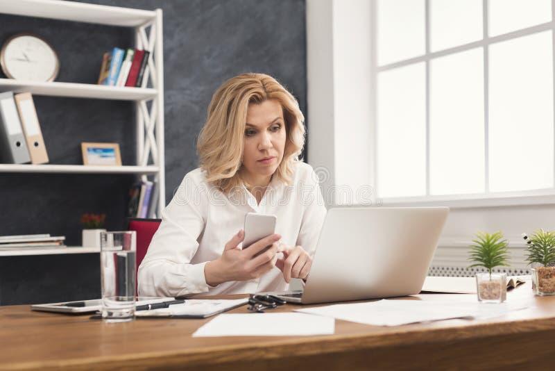 Poważny bizneswoman pracuje na laptopie przy biurem fotografia royalty free