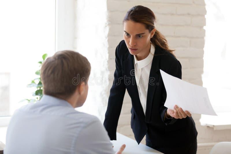 Poważny bizneswoman wini pracownika dla błędu w papierowym docu obrazy royalty free