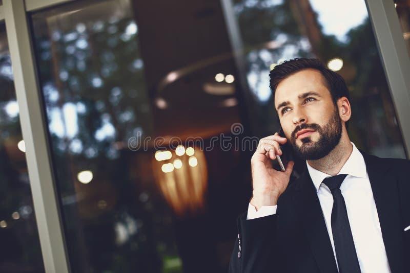 Poważny brodaty mężczyzna wyglÄ…dajÄ…cy spokojnie, rozmawiajÄ…c przez telefon zdjęcie stock
