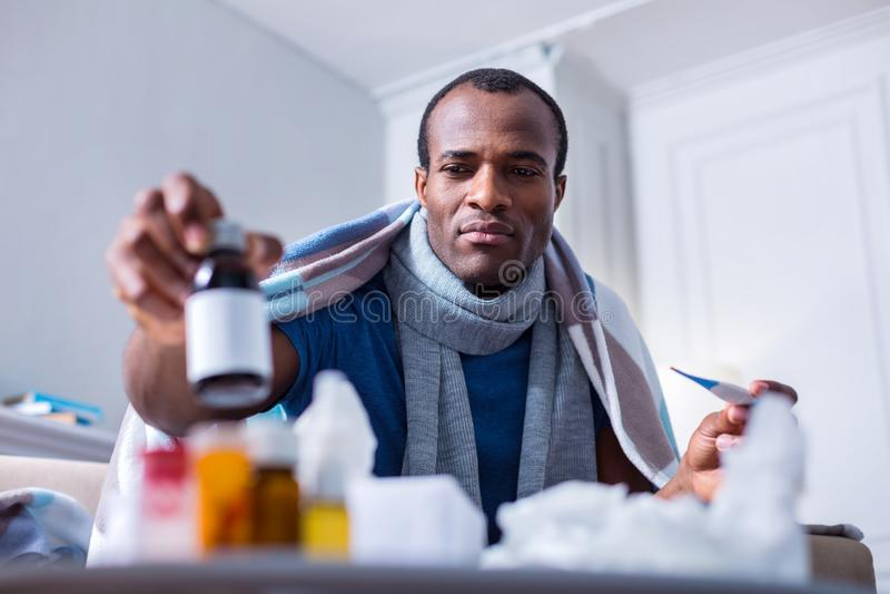 Poważny chory mężczyzna bierze butelkę z medycyną zdjęcia stock