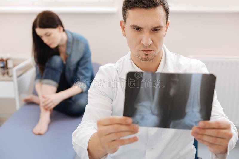 Poważny doświadczony rheumatologist trzyma X promienia wizerunek obrazy royalty free