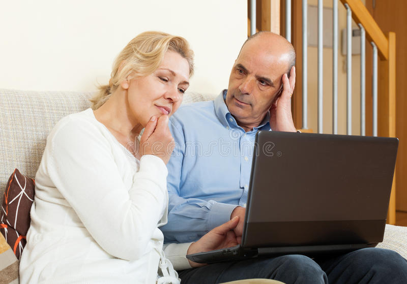 Poważny dorośleć pary z laptopem obraz royalty free