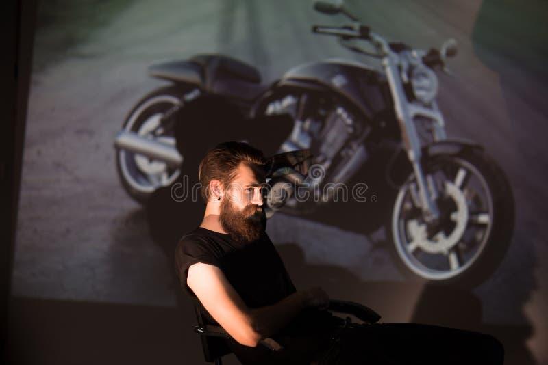 Poważny elegancki rowerzysty mężczyzna patrzeje przez obruszeń jego motocykl obrazy royalty free