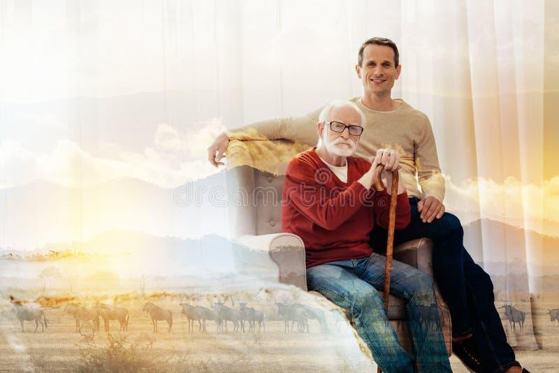 Poważny emeryta obsiadanie w karle podczas gdy jego syn jest blisko zdjęcie stock
