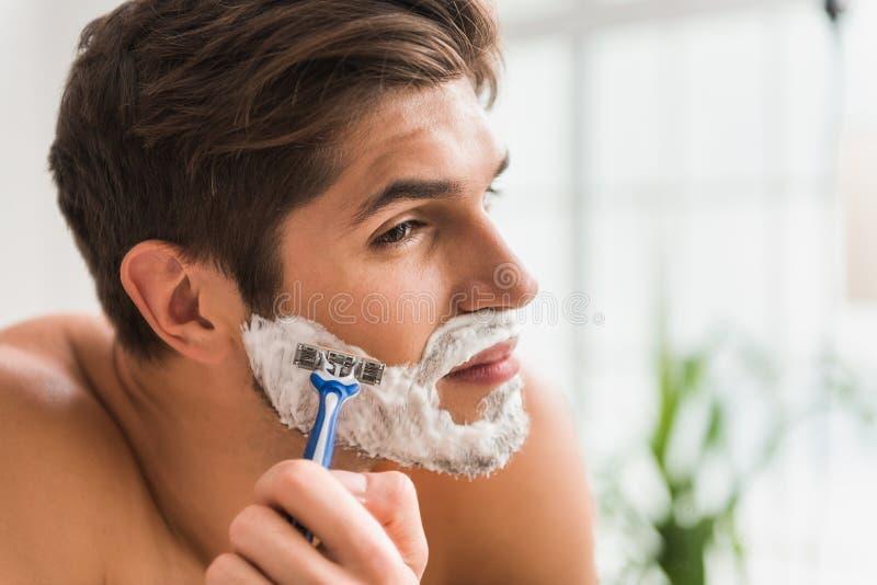Poważny facet goli jego brodę zdjęcie stock