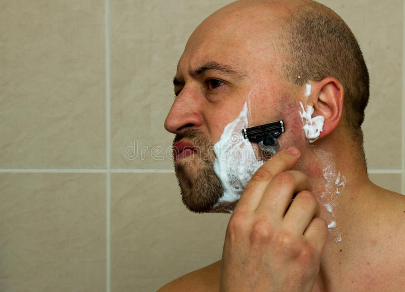 Poważny facet goli jego brodę fotografia royalty free