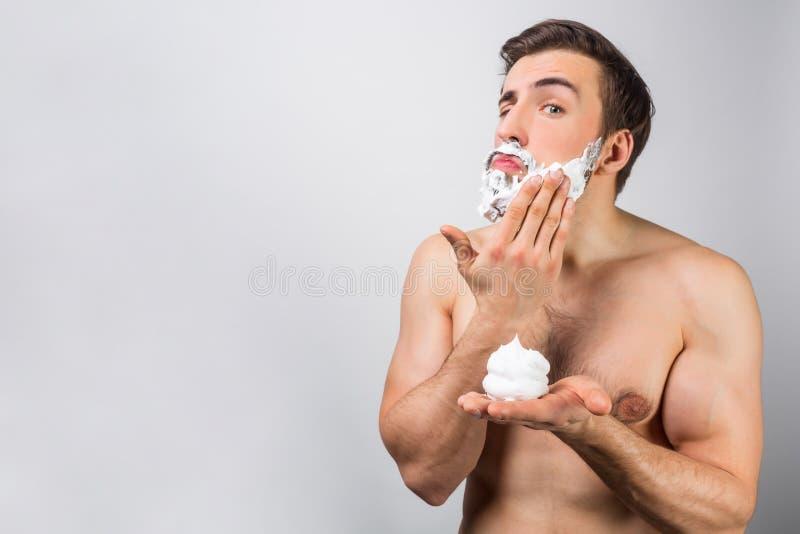 Poważny facet stawia niektóre ogolenia śmietanki ro ogolenie jego broda Ten prawie dzienna rutyna utrzymuje on w tonus Rżnięty wi fotografia royalty free