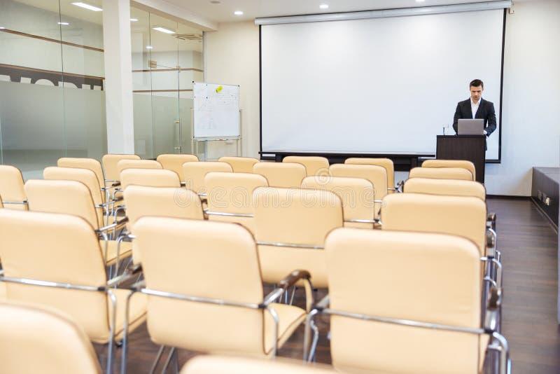 Poważny głośnikowy używa laptop w pustej sala posiedzeń obraz royalty free