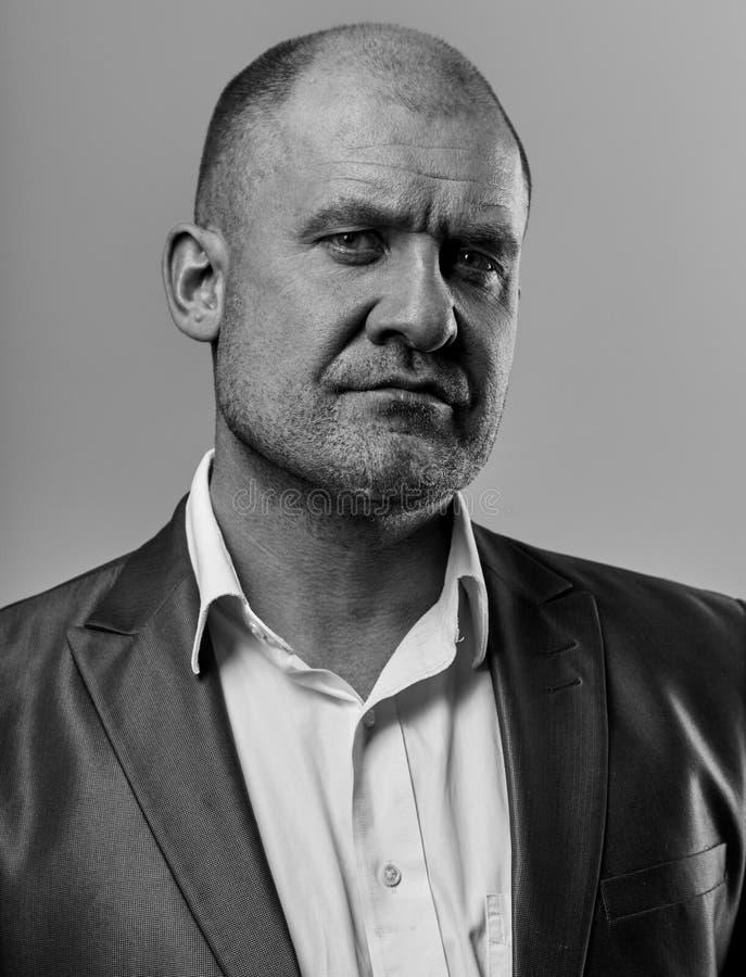 Poważny gniewny mężczyzna w kostiumu patrzeć Portret aktor na popielatym tle Emocjonalny naturalny portret zbli?enie zdjęcia stock
