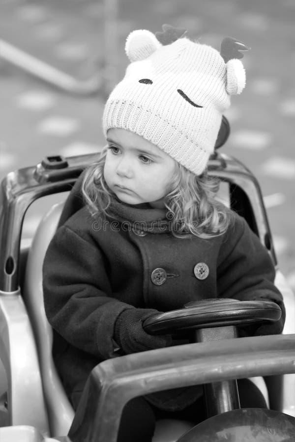 Poważny i baczny dziewczynka kierowca obserwuje ruchów drogowych przepisy Czarny i biały szczery portret dziecko w parku fotografia stock