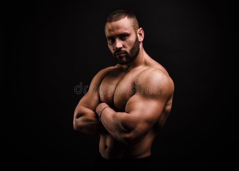 Poważny i bez koszuli bodybuilder ręk na mięśniowej klatce piersiowej na czarnym tle skrzyżowanie Budynków mięśni pojęcie fotografia royalty free