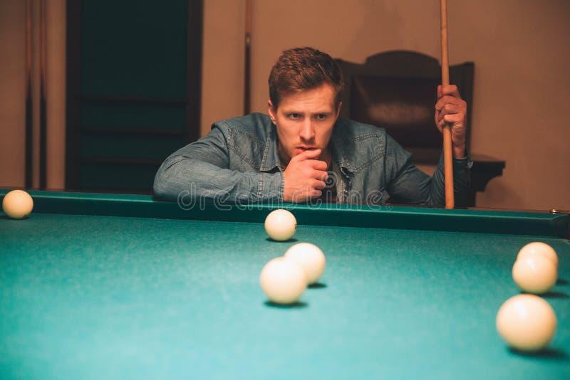 Poważny i skoncentrowany młodego człowieka główkowanie Patrzeje bilardowe piłki na łóżku stół Faceta chwyta bilardowa wskazówka J obrazy royalty free