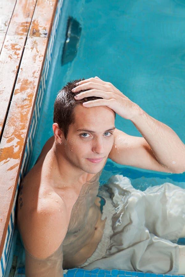 Poważny mężczyzna odpoczywa w krawędzi basen obraz royalty free