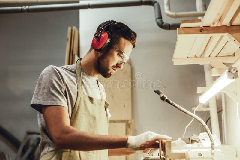 Poważny mężczyzna pracuje z drewnem w joinery zdjęcia royalty free