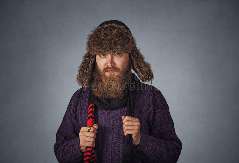 Poważny mężczyzna w futerkowym kapeluszu ubierał w puloweru mienia szalika czerwony pozować obrazy royalty free