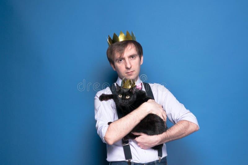 Poważny mężczyzna wewnątrz w różowej koszula, suspender i domowej roboty złotej koronie z ślicznym czarnym kotem w błysz zdjęcia stock