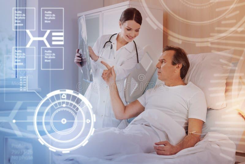 Poważny mężczyzna wskazuje X promień wynika podczas gdy opowiadający jego lekarka obraz stock