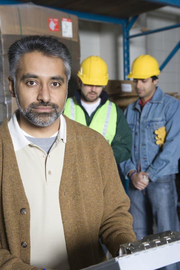 Poważny mężczyzna Z kolegami Behind W fabryce obrazy stock
