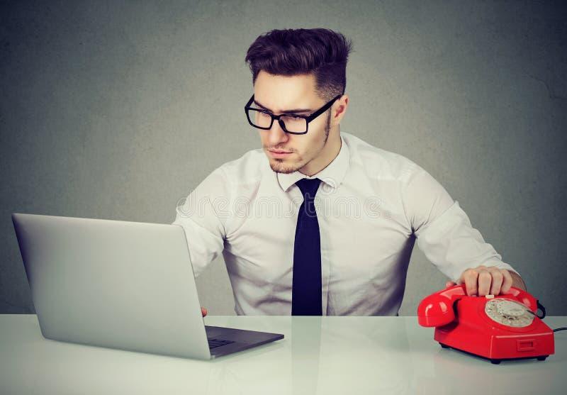 Poważny męski pracownik przy pracującym biurkiem zdjęcia royalty free